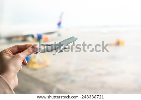 Close up hand holding an airplane model at airport - stock photo