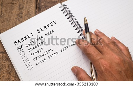 close up hand holding ball pen with text market servey.selective focus and shallow depth of field. - stock photo
