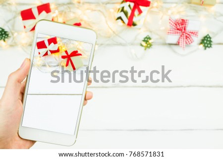 close up hand holding mobile smartphone take christmas new year theme red and craft gift box