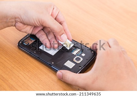 Close up hand holding  SIm card and smartphone on wood background - stock photo