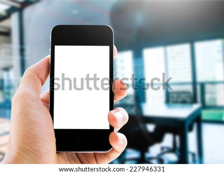 close up hand holding smart phone on meeting room background - stock photo