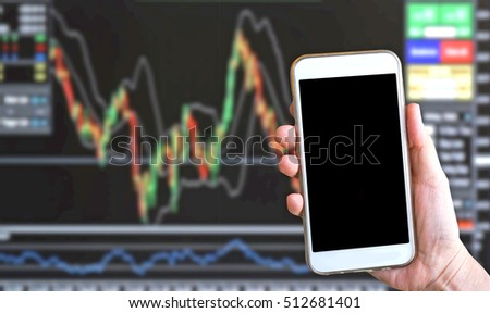 close up hand holding smart phone over blurred stock trade board chart economics background- business or economy concept