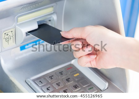 Close up hand inserting card into ATM.