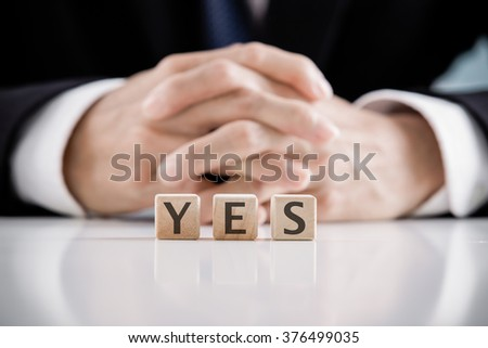 Close up Hand of a Businessman Arranging Small Wooden Blocks with yes words on blocks