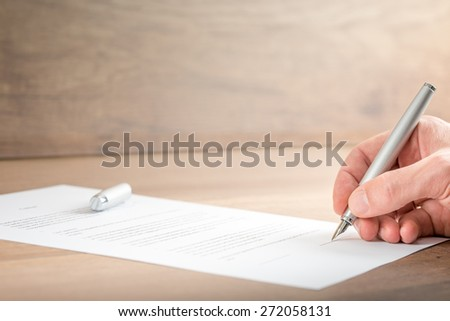 Close up Hand of a Businessman Signing a Contract Document on Top of a Wooden Table. - stock photo