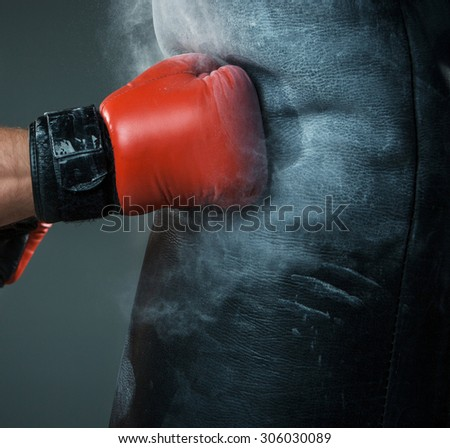 Close-up hand of boxer at the moment of impact on punching bag over black background - stock photo