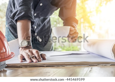 Close up hand of engineer holding a pen, cup of coffee and check blue print. - stock photo