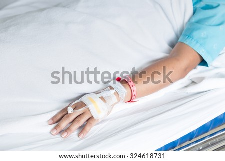 Close up hand of female patient with IV drip needle piercing in hospital room