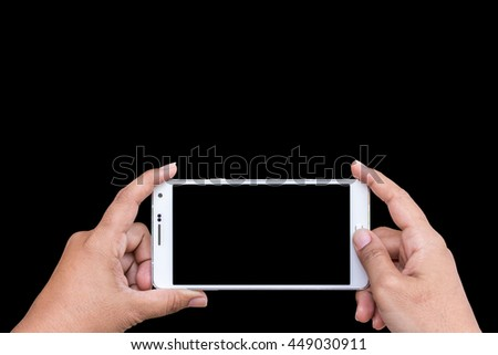 Close up hand of woman holding smartphone isolated on black background. Saved with clipping path