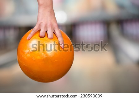 Close-up hand of woman is holding ball against bowling alley. - stock photo