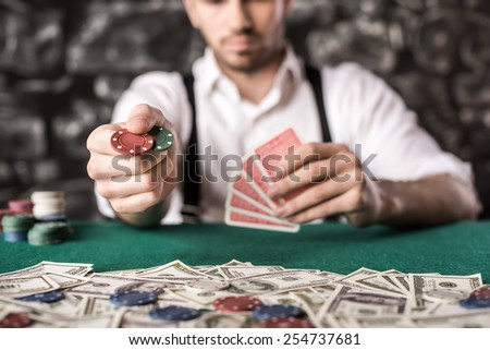 Close-up hand of young gangster man, while playing poker game, with money, chips and cards. - stock photo