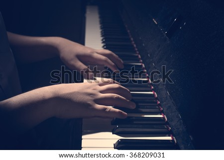 close up hand on piano in low key image - stock photo
