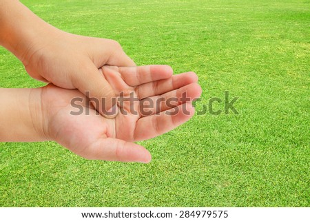Close up hand pain on green grass background - stock photo