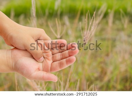 Close up hand pain with blurred grass background