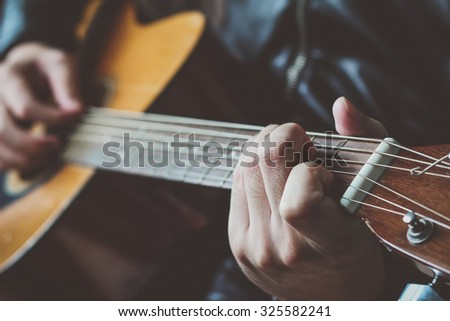 close-up, hand playing on acoustic guitar, playing chord C major position  - stock photo