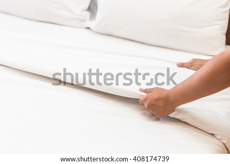 Close up hand set up white bed sheet in hotel room - stock photo