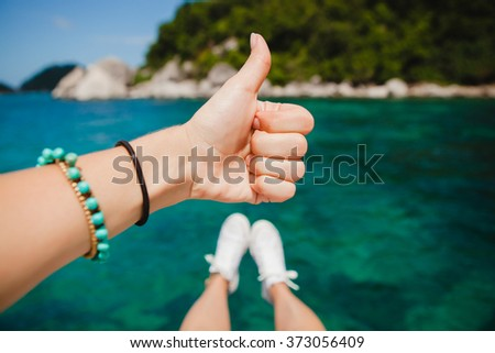 close up hand showing thumb up, beautiful sea view, tropical island vacation, blue lagoon landscape, legs, positive mood, cool, traveling, sunny summer, first-person, self photo - stock photo