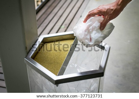 Close-up, Hand throwing plastic bag into recycling bin, concept of environmental protection, Keep clean, Littering of environmental. - stock photo