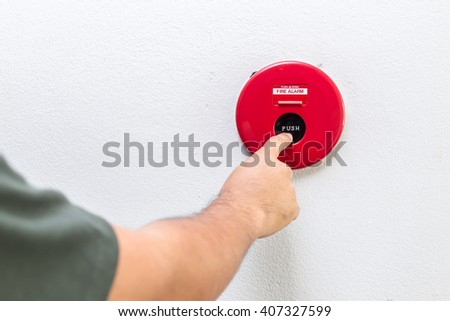Close up hand with finger pressing red fire alarm on the wall - stock photo