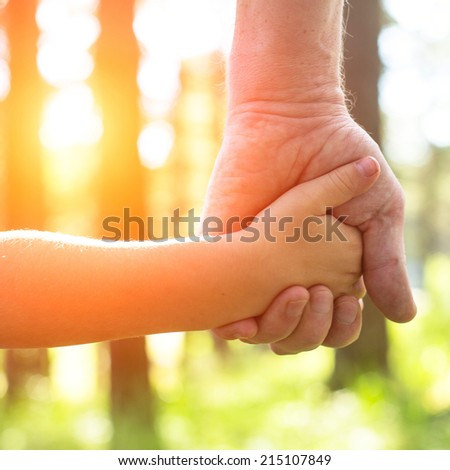 Close-up hands, an adult holding a child's hand, nature and sunset in background. - stock photo