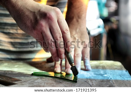 close up hands cutting green glass for stained glass artwork - stock photo