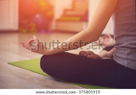 Close up hands. Girl do yoga indoors. Woman exercising yoga at sunset with a warmth background in gym. Young woman conducts meditating indoors. - stock photo