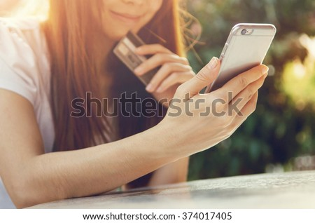 Close up hands holding credit card and using mobile smart phone outdoor, Online shopping, woman happy.
