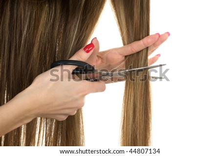 Close-up hands holding scissors trying to cut long hair - stock photo