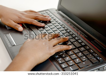 close-up hands of a black woman on a keyboard