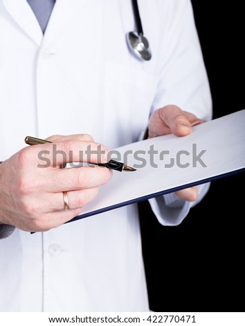 close-up hands of a doctor, he takes notes in a patient's medical history - stock photo