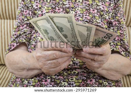 close up hands of a senior woman holding money - stock photo