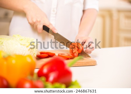 Close-up hands of a woman who cuts vegetables. - stock photo