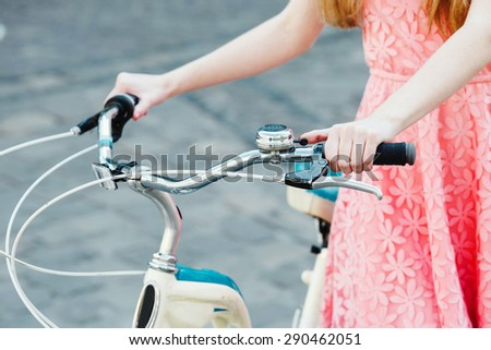 Close up hands of a young girl on old bicycle handlebar - stock photo
