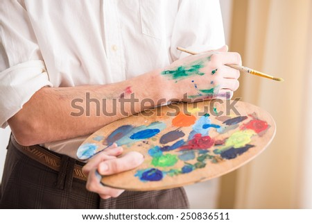 Close-up hands of artist with palette and brush. - stock photo