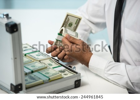 Close-up hands of businessman with suitcase full of money. - stock photo