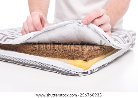 Close-up hands of man is showing mattress made of coconut fiber. - stock photo
