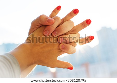 Close up Hands of Romantic Couple Holding Together with Sun Rays  - stock photo