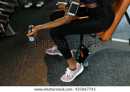 Close-up hands of sexy fitness african american woman working out with dumbbells at the gym and listens music in earphones - stock photo