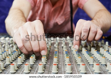 close-up hands of sound engineer work with faders and knobs on professional audio musical mixer - stock photo
