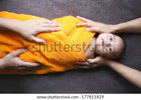 Close up Hands of two parents protecting their newborn baby - stock photo