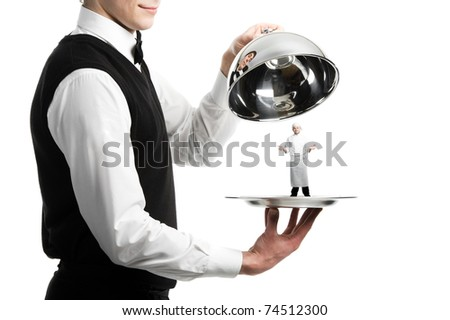 Close up hands of waiter with metal cloche and chef under it - stock photo
