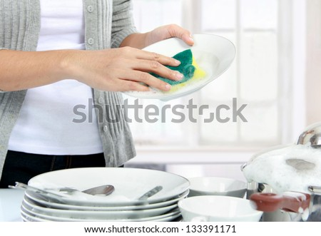 close up hands of Woman Washing Dishes in the kitchen - stock photo