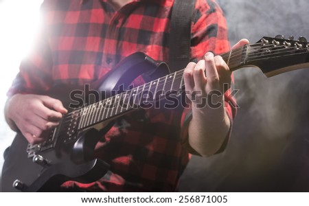 Close-up hands of young guitarist with the electric guitar, in dark room with light behind him.