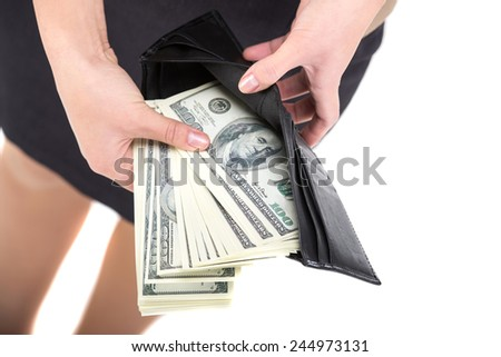 Close-up hands of young woman is holding full of money wallet, isolated on white background.
