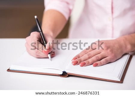 Close-up hands of young woman is writing in notebook at office.