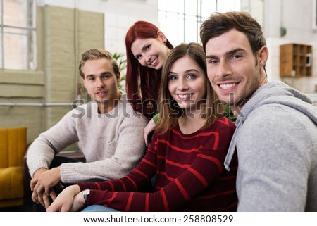 Close up Handsome and Pretty Young Close Friends in Casual Outfits Resting at the Sofa in Living Area, Smiling at Camera
