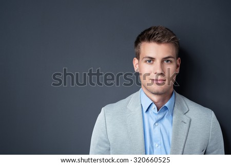 Close up Handsome Businessman Smiling at the Camera Against Gray Wall Background with Copy Space on the Left Side. - stock photo