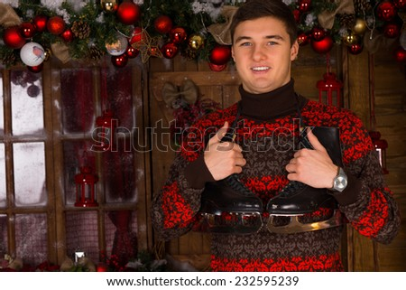 Close up Handsome Young Man in Winter Outfit Holding a Pair of Ice Skates in Front Christmas Decors on the Wall, While Looking at the Camera. - stock photo
