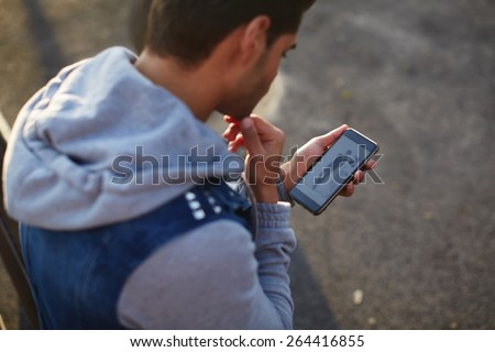 Close up handsome young man using smart phone while standing outdoors at sunny evening, rear view shot hipster man holding cell phone while looking to some fashion website on mobile screen - stock photo
