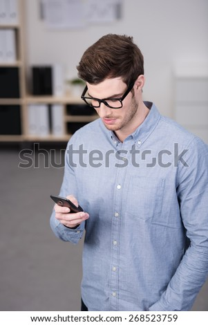 Close up Handsome Young Man, Wearing Long Sleeves Shirt with Eyeglasses, Busy at his Mobile Phone. - stock photo